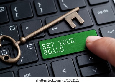 Closed up finger on keyboard with word SET YOUR GOALS
