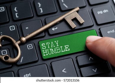 Closed up finger on keyboard with word STAY HUMBLE