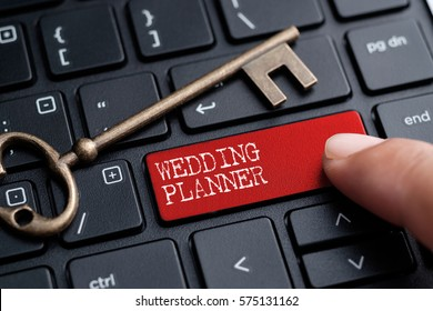 Closed up finger on keyboard with word WEDDING PLANNER