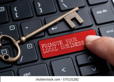 Closed up finger on keyboard with word PROMOTE YOUR LOCAL BUSINESS