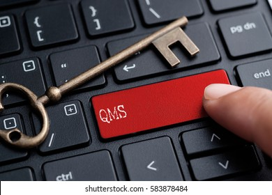 Closed up finger on keyboard with word QMS (Quality Management System)