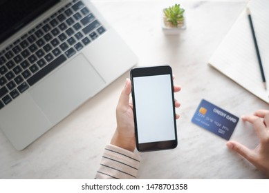 Closed up and focus on hand of young woman using a smartphone which show white display other hand will hold credit card and have notebook put on table in near. see top view. co working space concept.