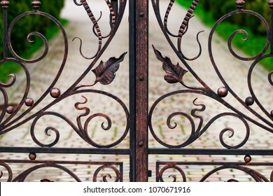 A closed forged metal gate looking onto a garden path.
