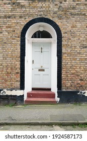 A closed front door with an arched top and stone steps.