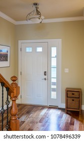 Closed front door leading onto wood steps with lobby or hall with hardwood flooring