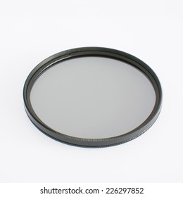 Closed up of glass circular filter over white background.