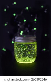 Closed green light glowing jar in the dark  background with sparkling bokeh