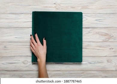 closed green wedding photo album isolated on wooden background. person opens a photobook. womans fingers touch a bright family photoalbum. womans hand holding family photo album with beautiful pattern
