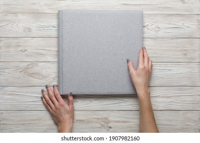 closed grey wedding photo album isolated on wooden background. person opens a photobook. womans fingers touch a family photoalbum. womans hand holding beautiful family photo book with space for text