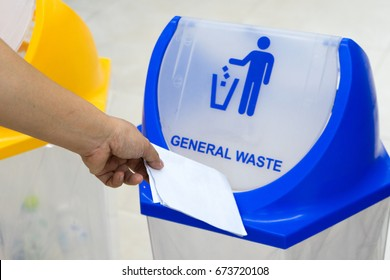 Closed up hand throwing waste paper into general waste recycle garbage trash