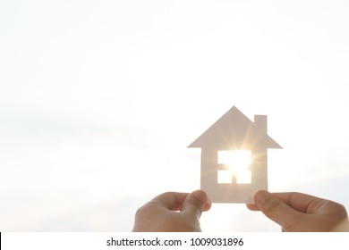 Closed up of hands holding paper house under the sunlight concept