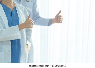 Closed up of happy doctor showing thumbs up ,medical staff at hospital, doctors team standing together ,gesture, health care, people and medicine concept ,with copy space for your text.