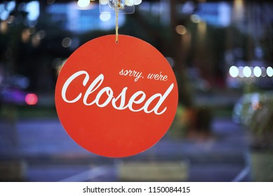 Closed for holiday. Sorry we are closed red circle round tag hanging on a glass of storefront.