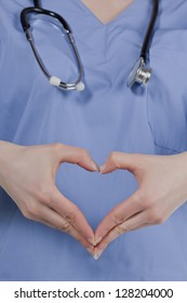 Closed up image of a doctor forming a heart shaped using her hands