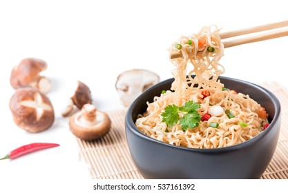 closed up instant noodles with vegetables on chopstick isolated on white background, junk food or fast food concept.