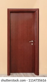 Closed interior brown wooden room door with metal handle