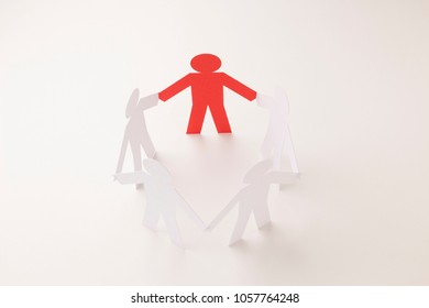 closed joining of five paper figure with red one in hand down posture on bright white background. in concept of business and leadership. selective focused point