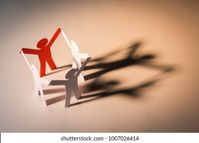 closed joining of four paper figure in hand up posture on light background. in concept of cooperation, successful and leadership.