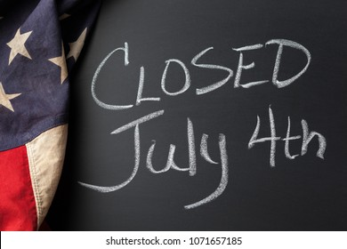 Closed July 4th sign handwritten on a chalkboard bordered by a vintage American flag