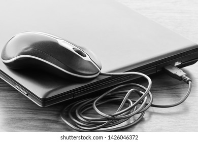 Closed laptop and mouse after successfully accomplished work in black and white colors