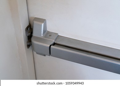 Closed up latch and door handle of emergency exit. Push bar and rail for panic exit.