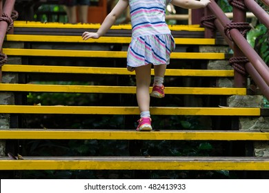 Closed up little girl climbing up stairs outdoors