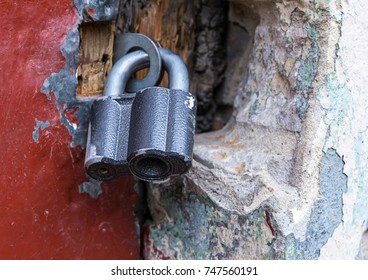 closed lock hinged metal black hanging on hinges on a stone background and red wooden door