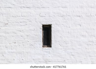 Closed loophole, embrasure in an old white brick wall