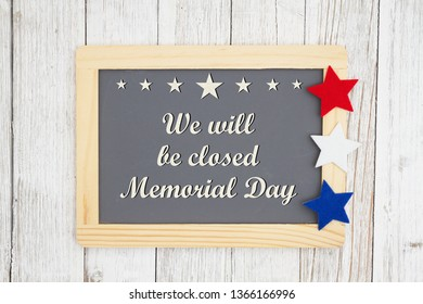 Closed Memorial  Day chalkboard sign, We will be closed Memorial Day text on a chalkboard with patriotic USA red and blue stars on weathered whitewashed textured wood