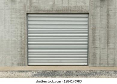 Closed metallic garage door in a grey industial wall
