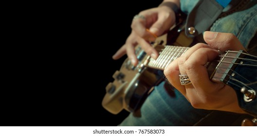 closed up musician playing electric guitar on black background concept