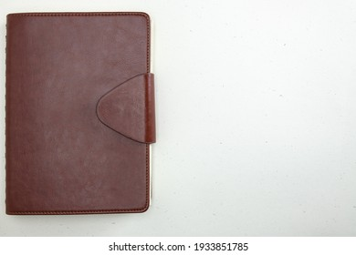 closed notebook in a leather cover with a clasp on a light background a place for text