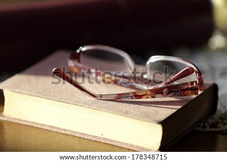 Closed old book and glasses, on home wooden table.