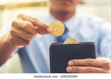Closed up on businessman right hand holding bitcoin, another half bitcoins on wallet left hand. Golden bitcoin coins in man's hands. Virtual currency. New virtual money.