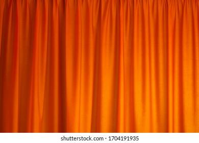 Closed orange drapes with satin velvet light effect for background