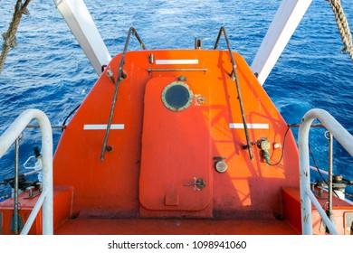 Closed orange lifeboat on a cargo ship.