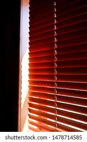Closed orange plastic blinds with sunlight in the morning. window with blinds. Interior design of living room with window horizontal blinds. Window with Sun-protection jalousie