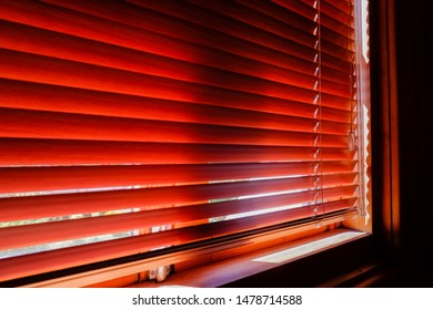 Closed orange plastic blinds with sunlight in the morning. window with blinds. Interior design of living room with window horizontal blinds.Closed jalousie on sunny day. Shadow and light