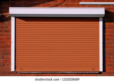 Closed orange serving hatch security shutters with brick background
