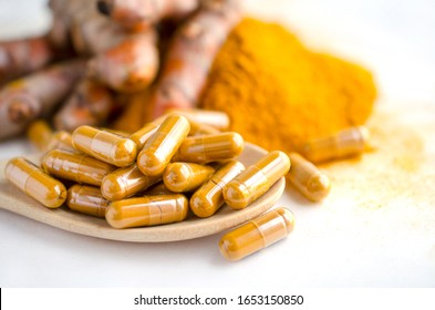 Closed up organic turmeric or curcumin powder in capsule on wooden spoon over blur background of fresh turmeric plant and powder pile on white background,for Thai herb or traditional medicine concept