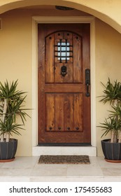 Closed ornate wood door of an upscale home, accented with an iron barred window, iron door knocker, and iron bolts. The door is set into a beige stucco house, framed with a wide arch and planters.