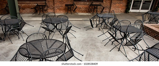 Closed outdoor seating area of an urban restaurant with iron chairs put up leaning against tables.
