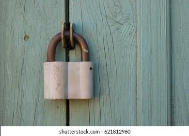 Closed padlock hanging on a wooden door