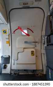 a closed Passenger airplane entrance door - inside view - with the inflatable emergency evacuation slide in armed position - door 1L