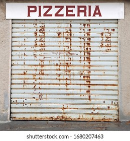 closed portcullis of the pizzeria due to the world economic crisis and the big text