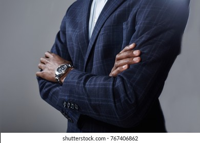 Closed posture. Close-up of hands of confident african businessman in suit is standing with crossed arms. Selective focus. Isolated background
