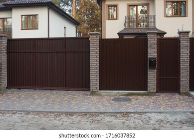 closed private brown metal gate and part of a brick fence