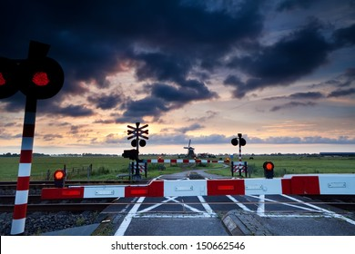 closed rail crossing with red signals at sunrise and windmill