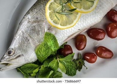 closed up of raw barramundi or asian seabass with tomatoes, sliced lemon and other gourmet on white plate. Cooking concept