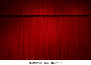 closed red stage curtains with a spot light on them